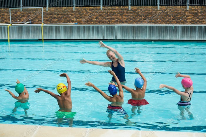 Instructor teaching children in swimming pool
