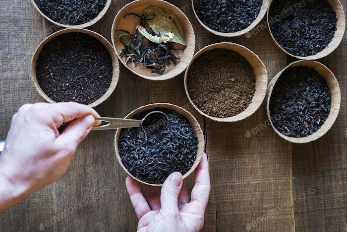 Hoher Winkel Nahaufnahme einer Auswahl von Teeblättern in kleinen Holzschalen.