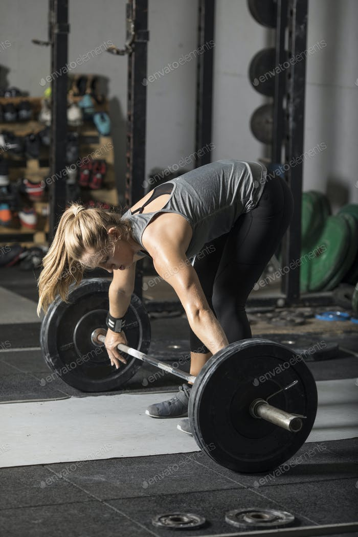 Young strong woman preparing to lift heavy barbell in gym.