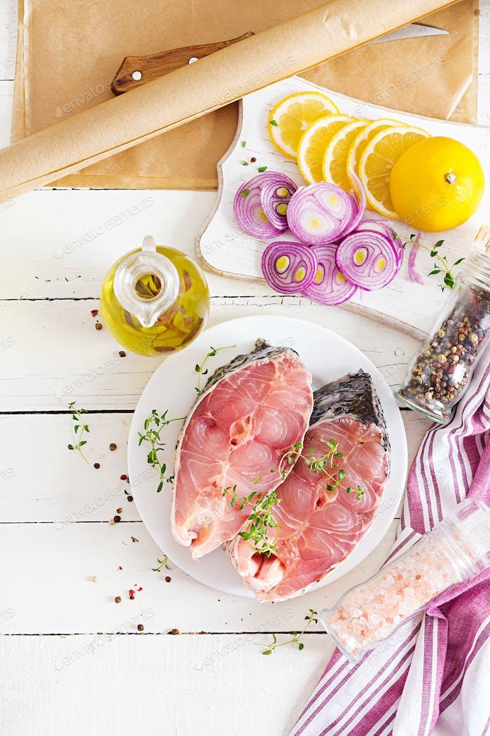 Rohes Steak aus Karpfenfischen mit Zitrone und Thymian auf weißem Holzhintergrund.