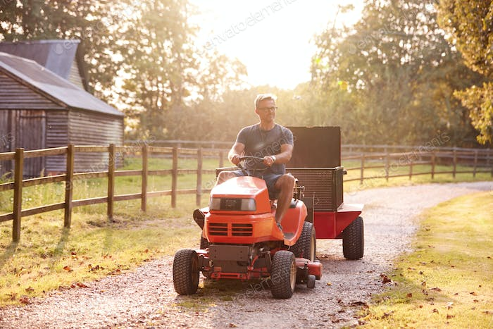 Mature Man Driving Ride On Mower Along Garden Path