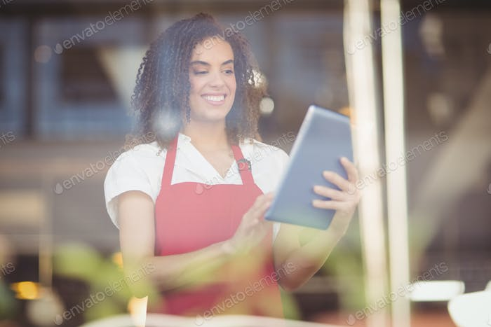 Smiling waitress using a digital tablet at the coffee shop