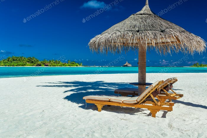 Two chairs and umbrella on a beach with shadow from palm tree