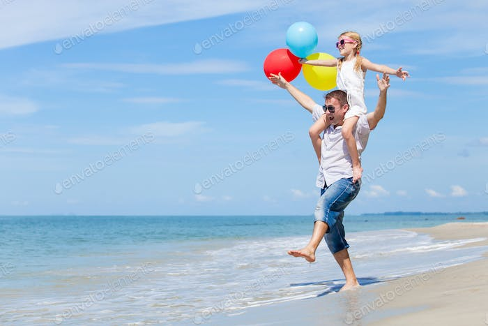 Father and daughter with balloons playing on the beach at the da