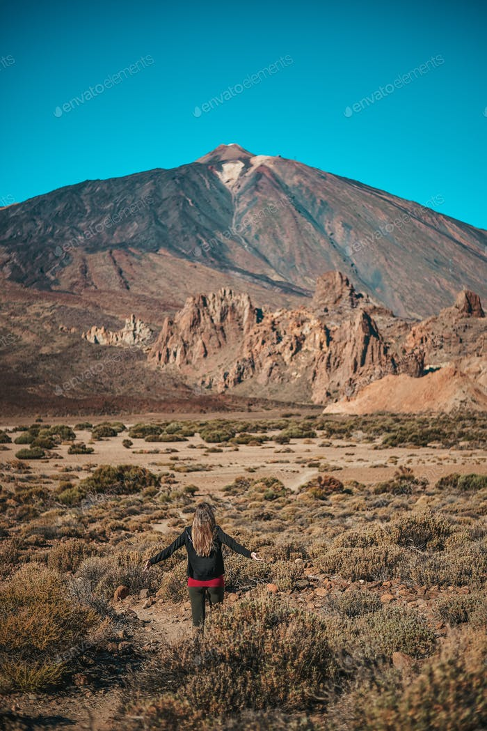 Young woman contemplating Roques de Garcia formation with the Teide volcano in the background