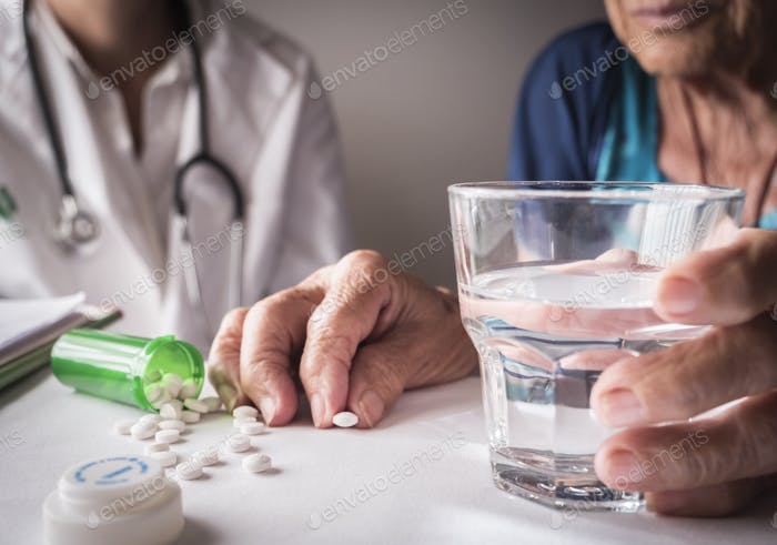 Oldster taking daily medication dose at home, Andalusia, Spain