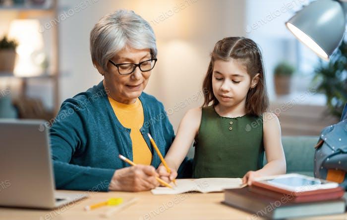 Girl studying with grandma.