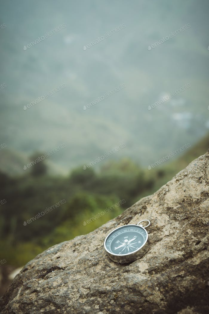 Trakking concept - Analogical Compass laying on the rocks with mountains in background