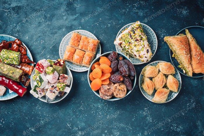Nahöstliche Süßigkeiten auf dunklem Hintergrund. Arabische Dessert, Baklava, Halva, rahat lokum, Sorbet, Nüsse