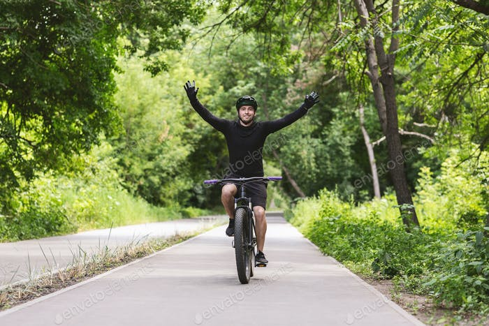 Young male cyclist celebrating victory with hands up