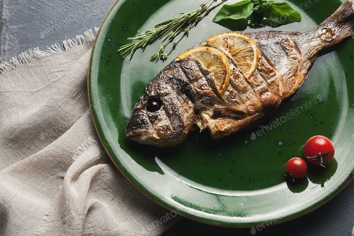 Whole grilled dorado with lemon slices on plate