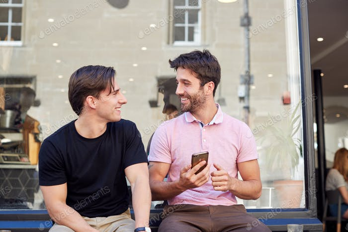 Male Gay Couple Sitting Outside Coffee Shop Looking At Social Media On Mobile Phone