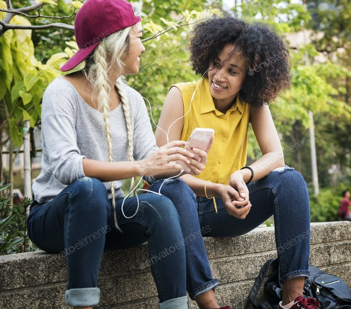 Young adult female friends listening to music through their smar