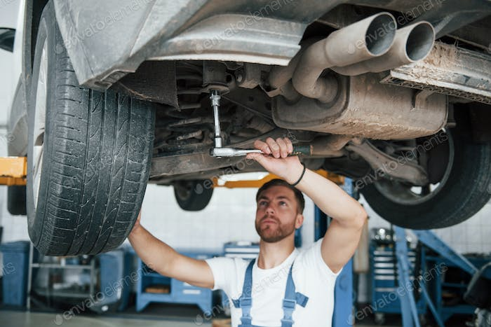 Shock absorbers on photo. Employee in the blue colored uniform works in the automobile salon