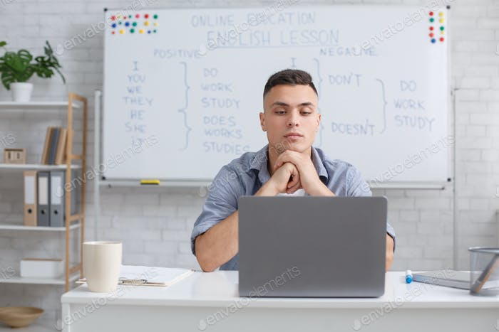 Communicate with students online remotely and video call with teacher. Concentrated man looking at
