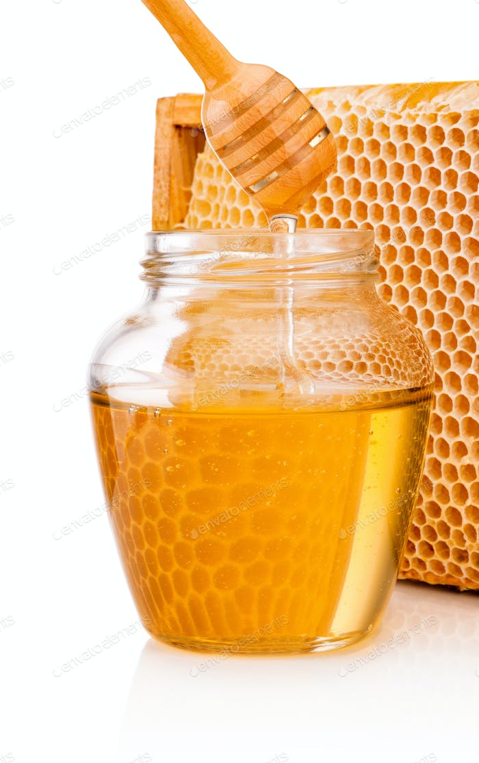 Honey dripping from dipper into glass jar on background honeycom