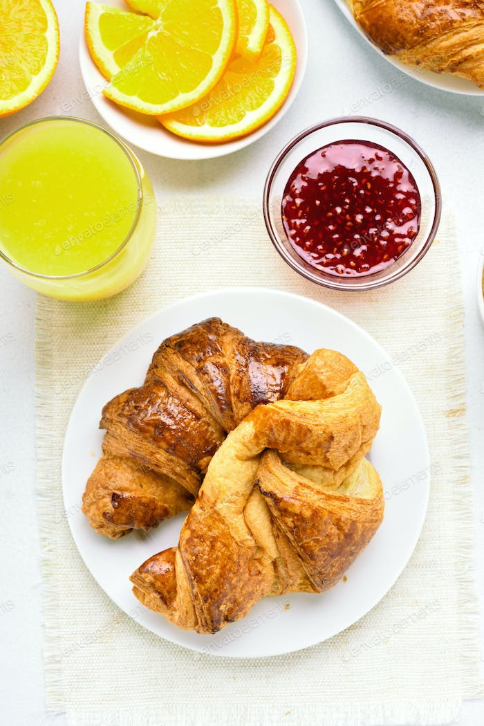 Breakfast with croissants, orange juice, raspberry jam