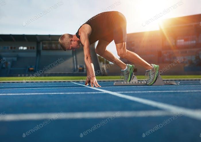 Junger Mann auf Startposition kurz vor dem Laufen