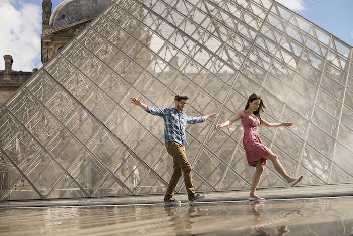 Ein Paar im Innenhof des Louvre-Museums, bei der großen Glaspyramide. Brunnen und Wasser.
