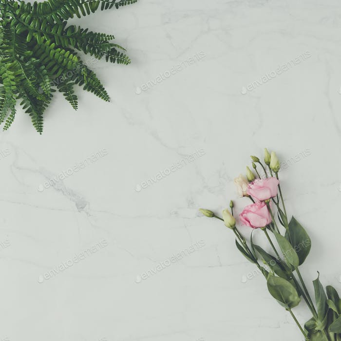 Creative natural composition made of flowers and leaves on marble background. Flat lay.