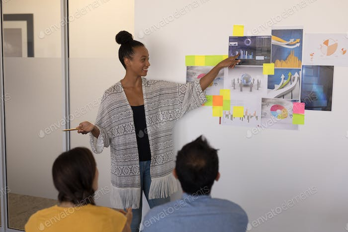 Female executive explaining graphs and sticky notes to diverse business team in modern office