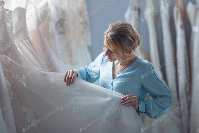 Attractive girl chooses a wedding dress in the store