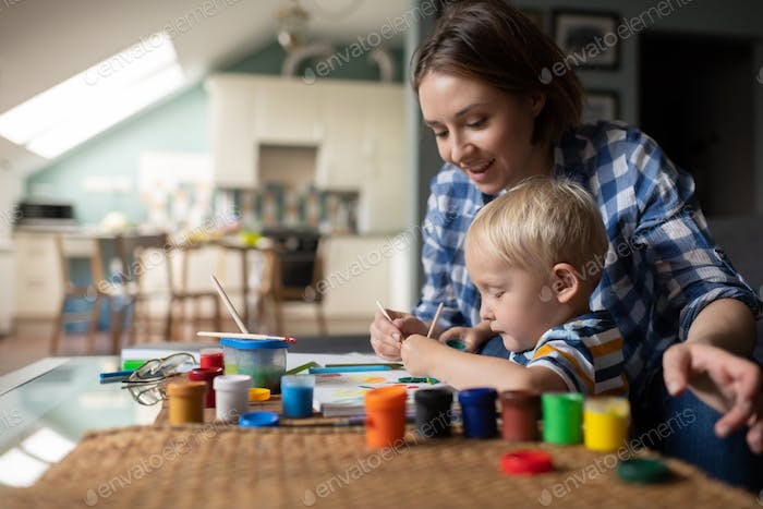 Content mother instructing to draw little son at home