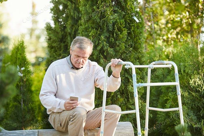 Senior Hombre enestado caminante descanso en Parque