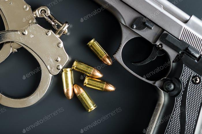 Pistolenkugeln, Handfeuerwaffe und Handschellen.