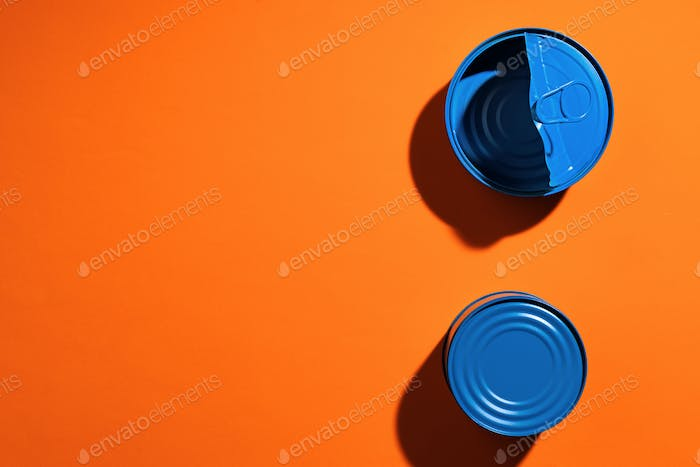 Aesthetic concept with blue painted tin can on orange background