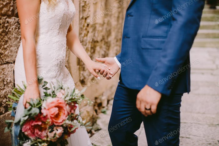 wedding couple holding hands with engagement ring