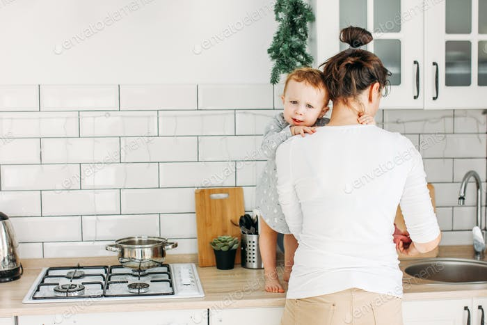 Young woman with baby girl on hands cooking breakfast on kitchen at home