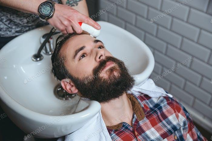 Man getting hairwash by hairdresser in hair salon