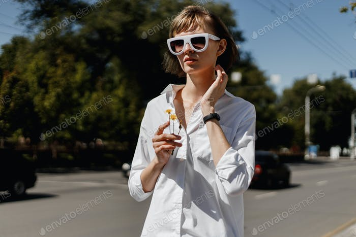 Stylish young woman in white sunglasses dressed in white shirt is standing with flower in her hand