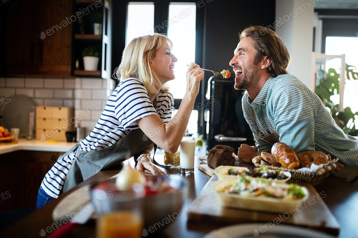 Beautiful young couple is smiling while cooking together in kitchen at home