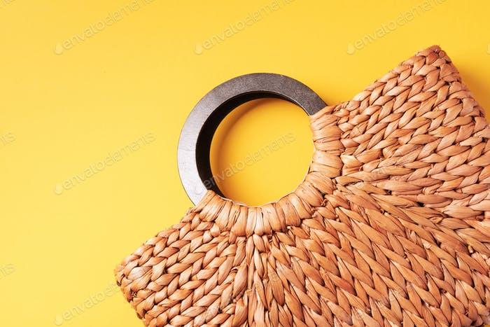 Handmade summer bag on trendy yellow background. Top view. Fashionable stylish accessory. Natural