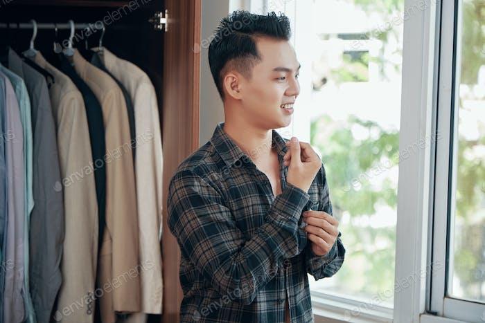 Smiling ethnic man dressing in morning time