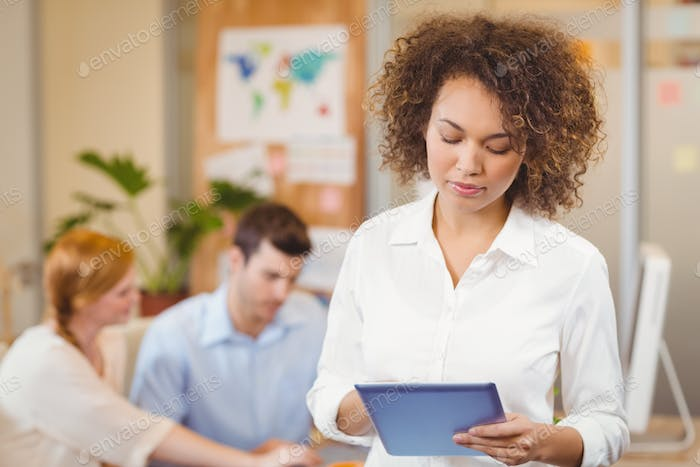 Businesswoman using digital tablet while colleagues working on laptop in background at office