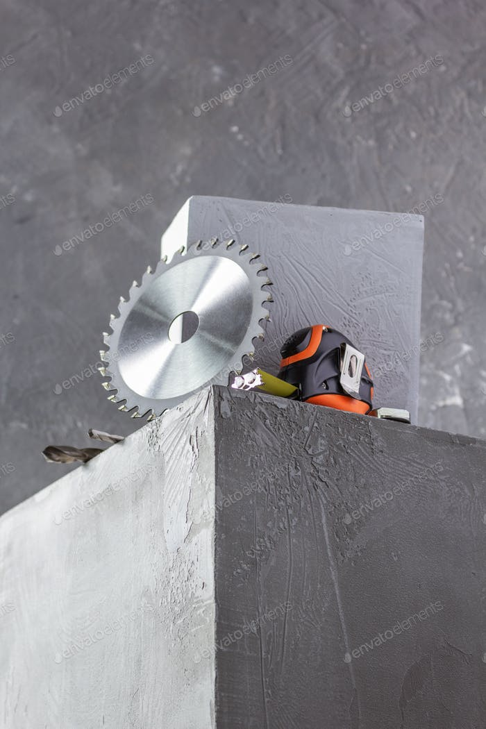 Circular saw blade and tools at concrete cube or construction blocks. Construction concept