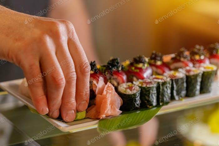 Chef decorating sushi rolls