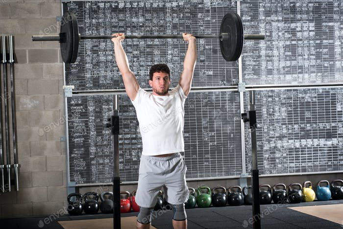 Strong bodybuilder lifting heavy barbell
