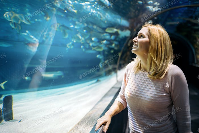 Woman in the aquarium watching the fish