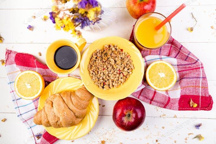 Gesundes Frühstück. Verschiedene Sortiments-Set. Orangensaft, Müsli, Croissant, Kaffee und Obst.