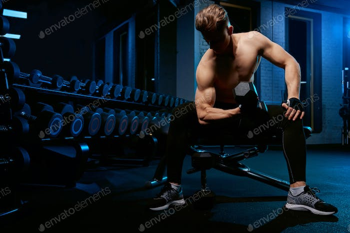 Muscular sportsman training arms with dumbbell