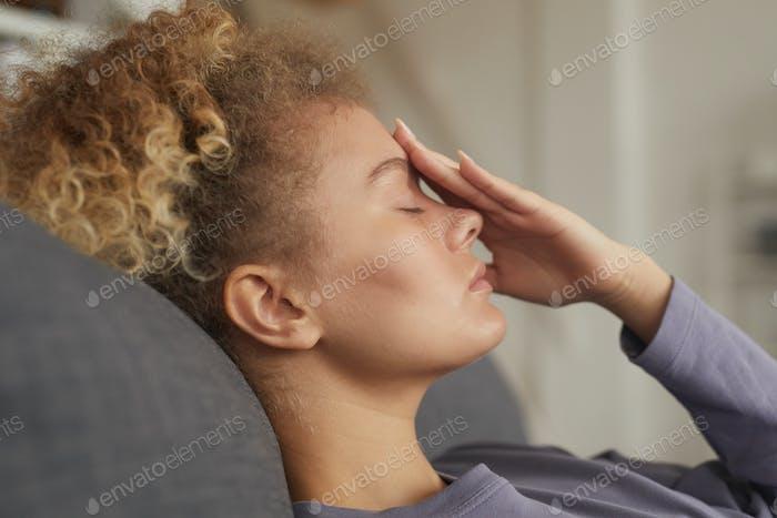 Tired woman lying on sofa