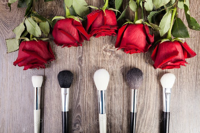 Conceptual image of make-up brushes next to roses