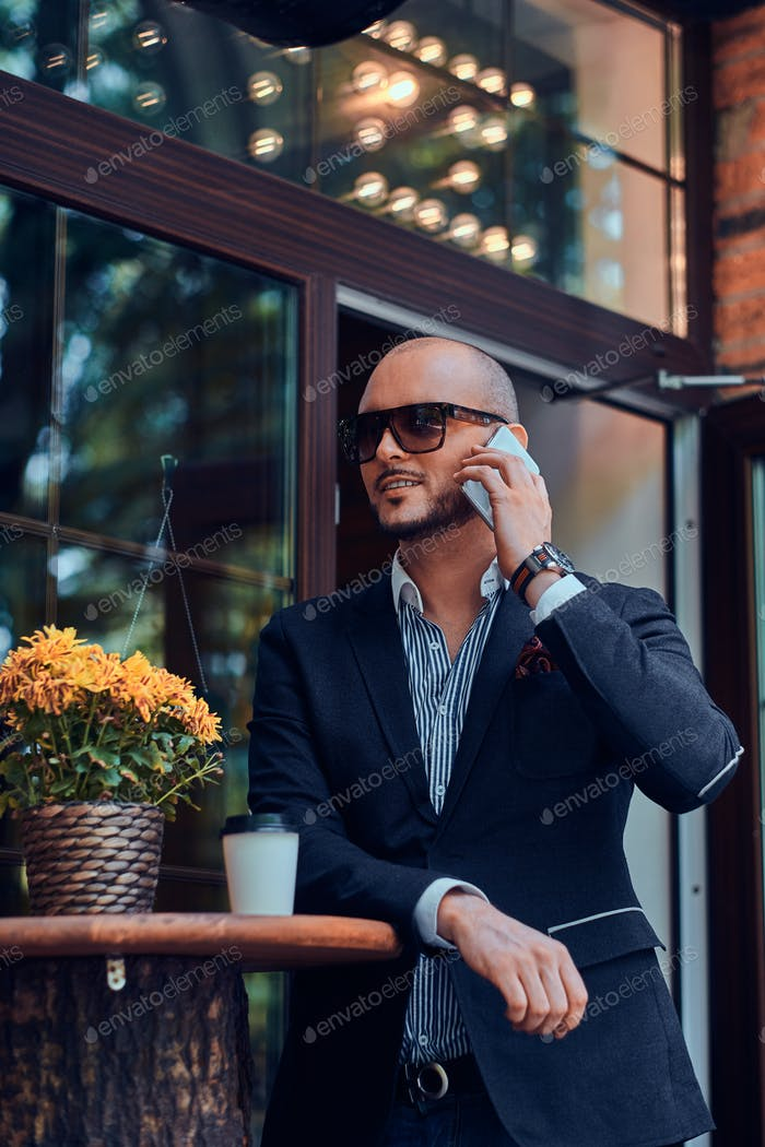 Успешный бизнесмен разговаривает по телефону, сидя в кофейне.
