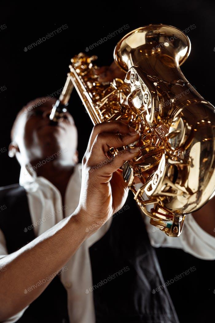 Афро-американский джазовый музыкант играет на саксофоне.