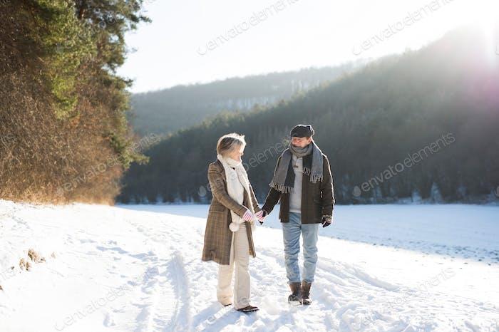 Beautiful senior couple on a walk on sunny winter day