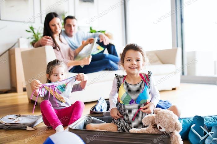Junge Familie mit zwei Kindern packen für den Urlaub.